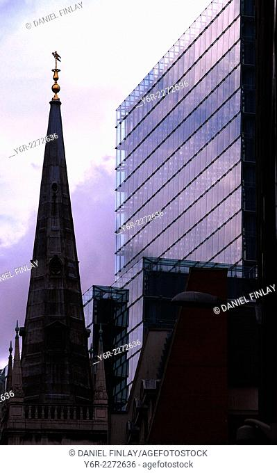 God and Mammon - church and office buildings in the City of London business district in moody evening light in London, England