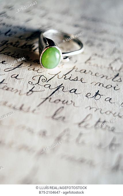 Engagement ring on top of a text of a handwritten letter