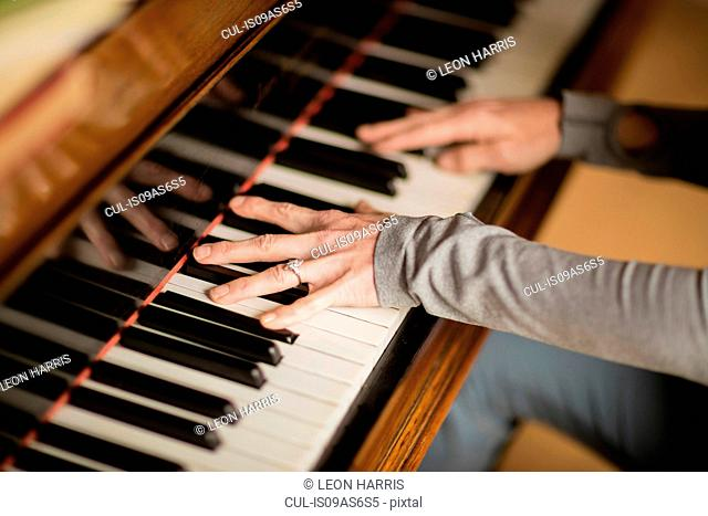Hands of mature woman playing piano