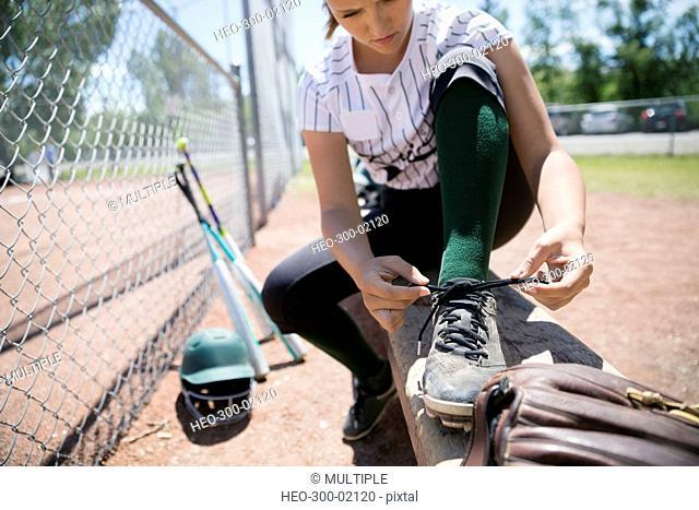 Middle school girl softball player tying shoe on bench