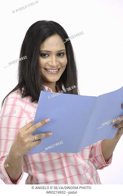 Young girl with hair open holding open book in her hand and smiling MR 703C