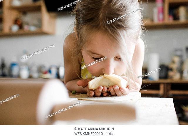 Little girl smelling freshly prepared stuffed pastry
