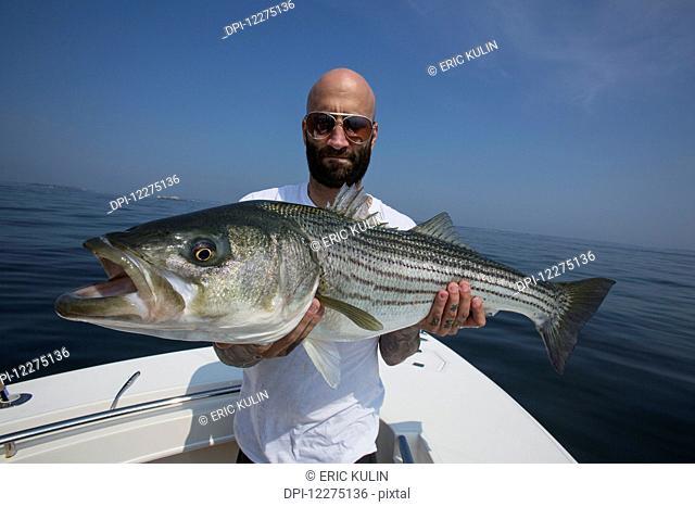Fisherman holding a large striper fish, Boston harbour; Boston, Massachusetts, United States of America