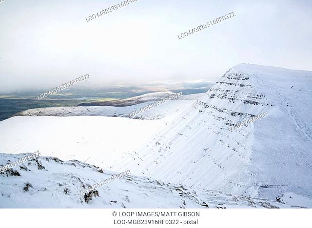 Stunning landscape views from top of deep snow covered mountains in Winter in cloud inversion
