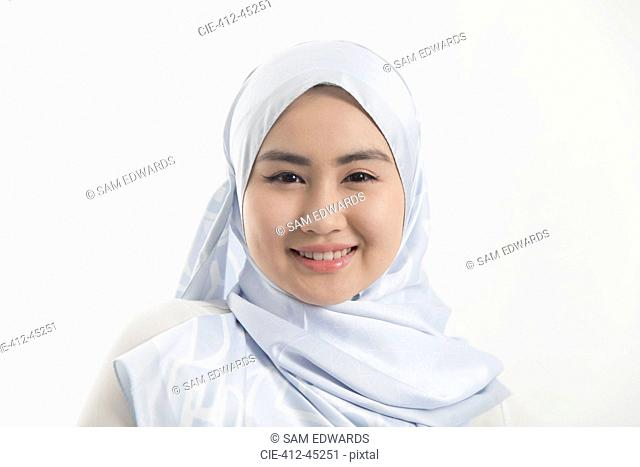 Portrait smiling, confident young woman wearing blue silk hijab
