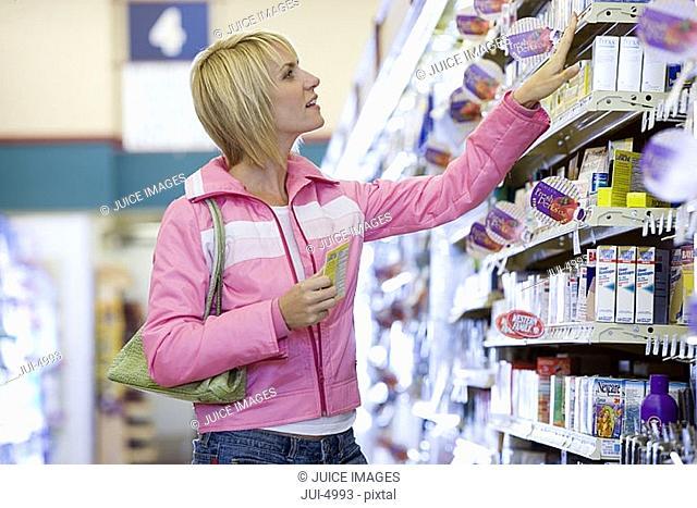 Woman shopping in supermarket, choosing item from shelf, side view