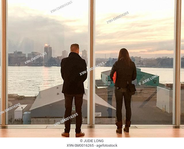 Man and Woman Couple Looking out a Window in Downtown Manhattan, New York City, Admiring the Western View of New Jersey