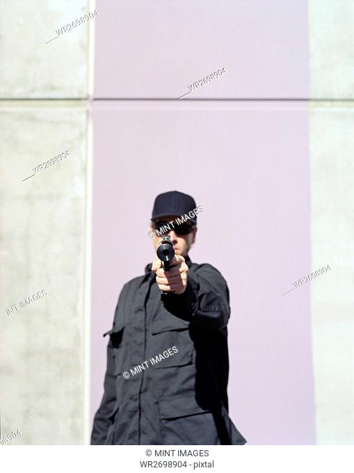 Man in special forces, aiming high powered hand gun with silencer attached