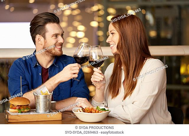 couple eating and drinking red wine at restaurant