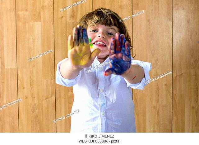 Portrait of smiling little boy showing his palms full of finger colours