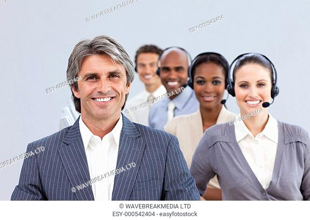 Confident manager in front of his team in a call center