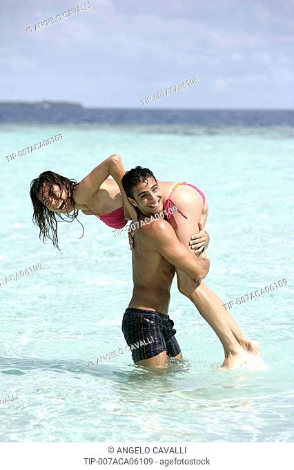 Couple at sea playing in shallow water