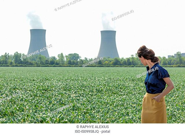 Woman in soy bean filed looking behind to nuclear power station