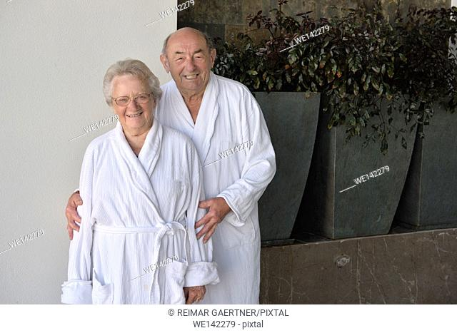Smiling senior couple in bathrobes on penthouse balcony in Mexico
