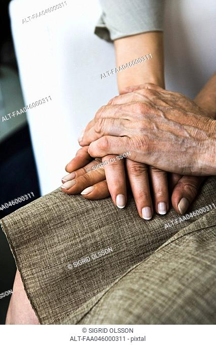 Senior woman holding adult daughter's hand, close-up