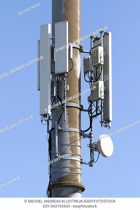 Cell phone tower or mobile cell site with blue sky background - The Netherlands