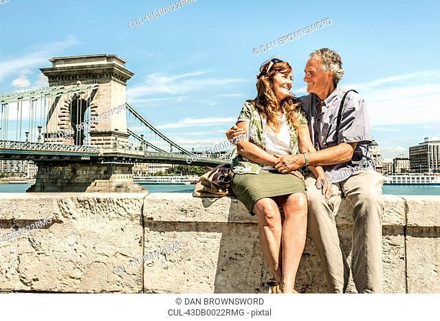 Older couple sitting on bridge