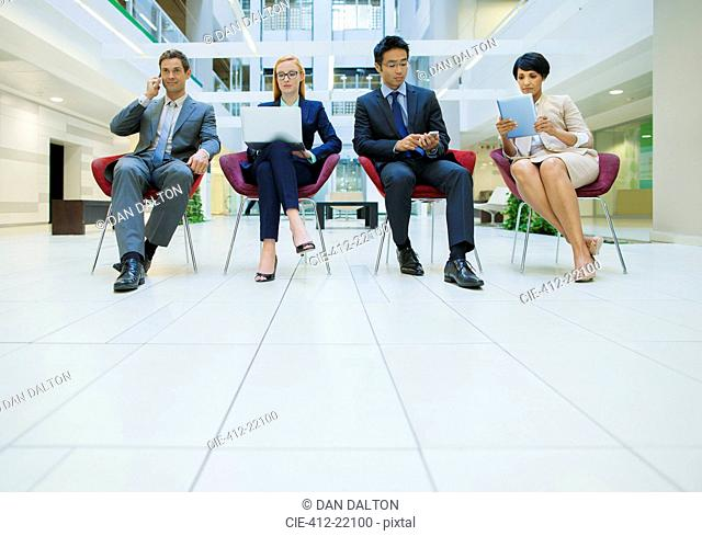 Business people sat in chairs working in office building
