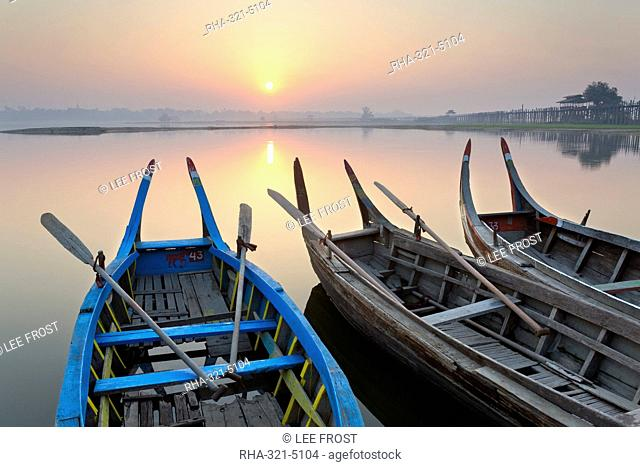 Traditional rowing boat moored on the edge of flat calm Taungthaman Lake at dawn with the colours of the sky reflecting in the calm water