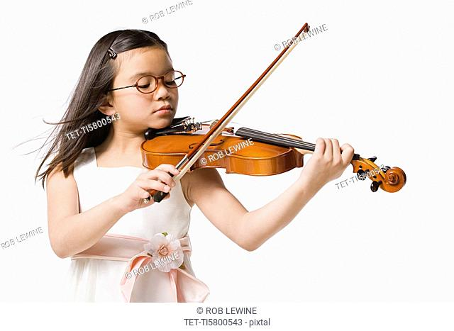 Studio portrait of girl 8-9 playing violin