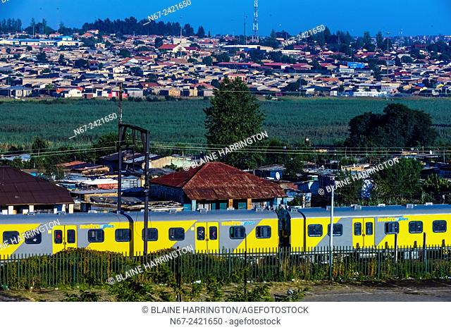 A train passes a shanty town in Soweto South Western Townships, Johannesburg, South Africa