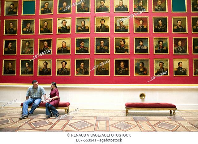 Couple seated in front of portrait gallery of the portrait gallery of the 1812 war heroes in the Hermitage Museum (Winter Palace). St Petersburg