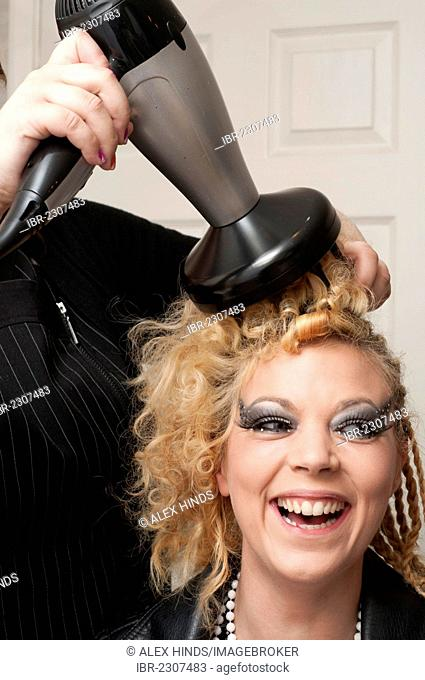Woman having hair dried at hairdresser's