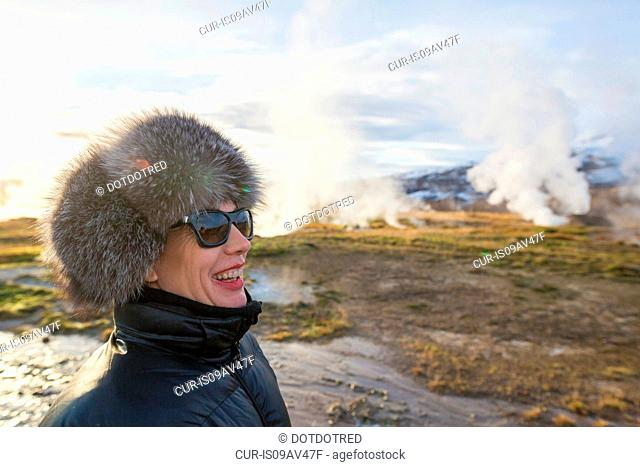 Woman at the area of The Great Geysir, a geyser that lies in the Haukadalur valley on the slopes of Laugarfjall hill, South West Iceland