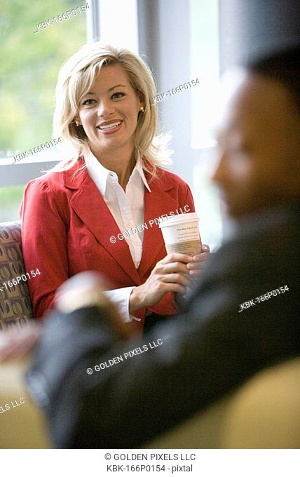 Portrait of a businesswoman sitting in an office lobby holding a coffee cup