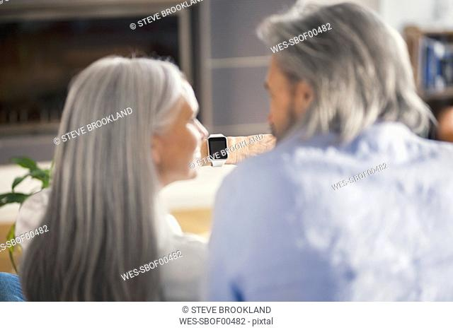 Senior couple looking at smartwatch