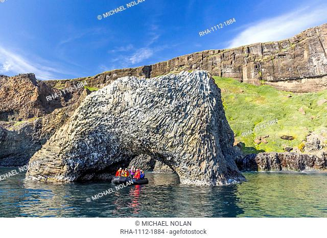 Zodiac cruises through a natural arch of columnar basalt on the southern coast of Disko Island, Kuannersuit, Greenland, Polar Regions