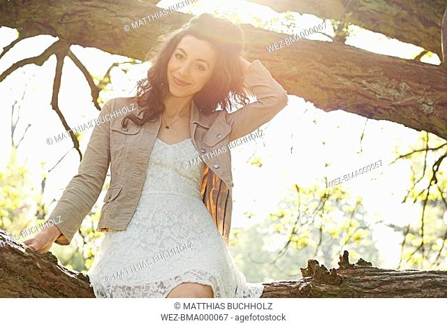 Portrait of smiling young woman sitting on a branch in a park at backlight