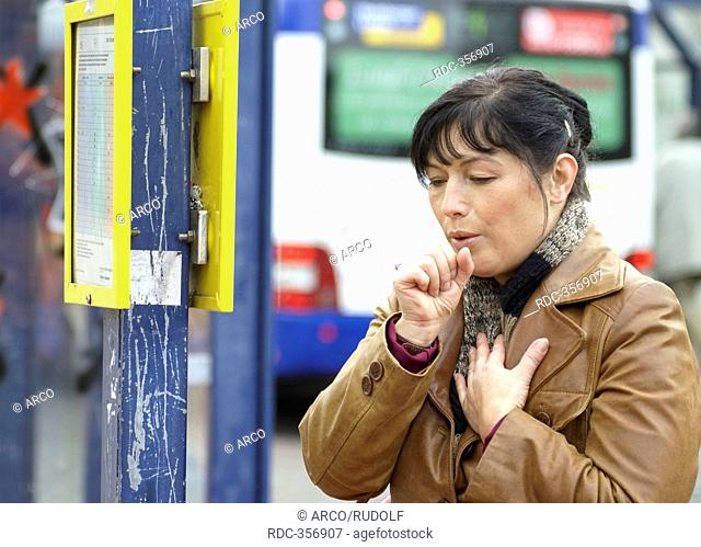 Woman coughing, at bus station, bus stop