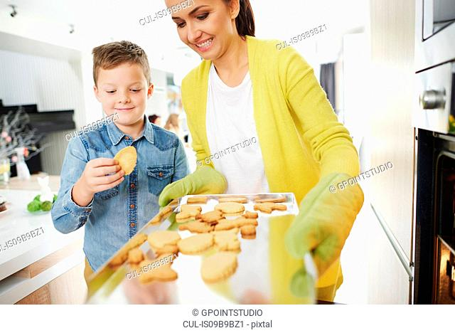 Boy pinching easter biscuit from mother's baking tray in kitchen