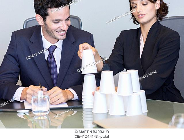 Business people stacking cups in meeting