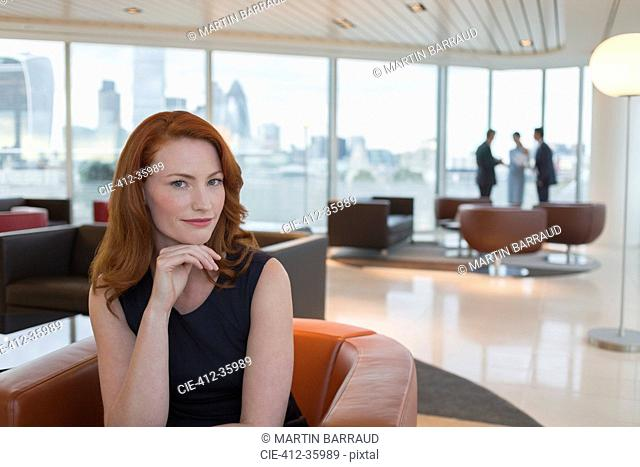 Portrait confident businesswoman with red hair in urban highrise office lounge