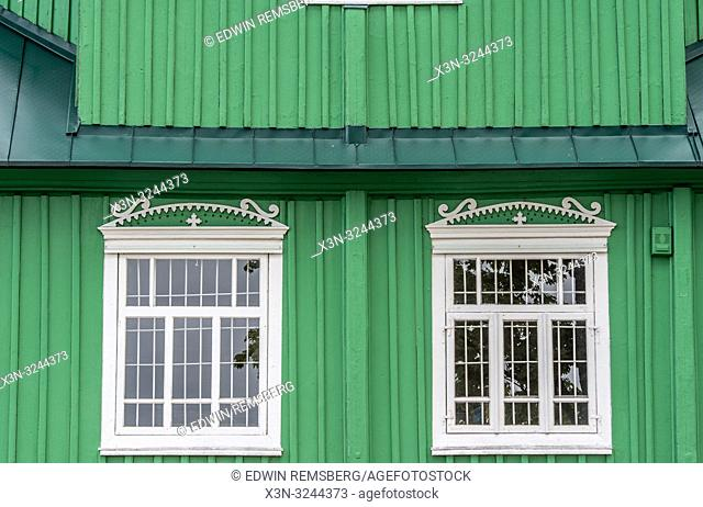 Exterior of green Russian Orthodox Church (Cerkiew Š›w. Michala Archaniola w Trzesciance) in the 'Land of the Open Shutters' with two windows, Trzescianka