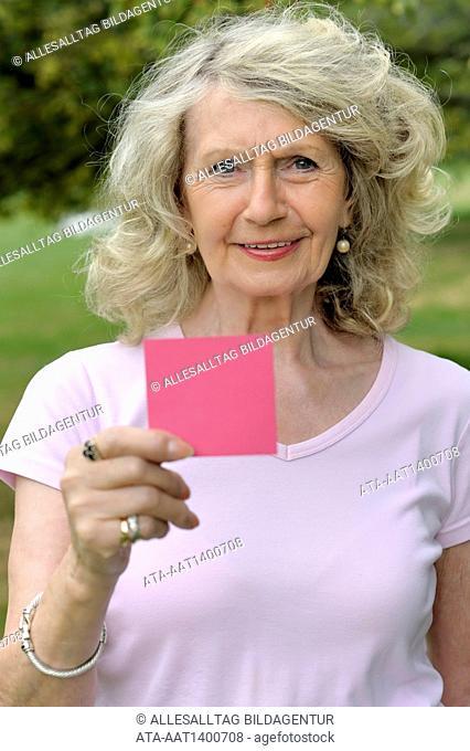 Elderly woman holding a blank card