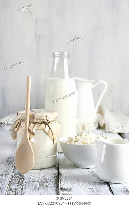 Various dairy products on rustic white wooden table: bowl of cottage cheese, jar of sour cream with wood spoon. bottle of milk and jugs