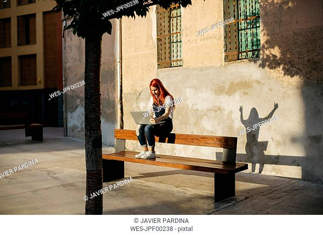 Redheaded woman sitting on bench using laptop