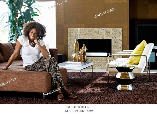 African woman sitting in modern living room