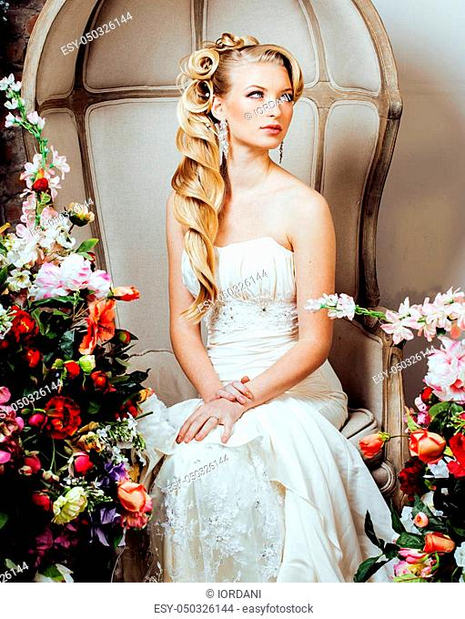 beauty emotional blond bride in luxury interior dreaming, crazy complicate hairstyle, many flowers