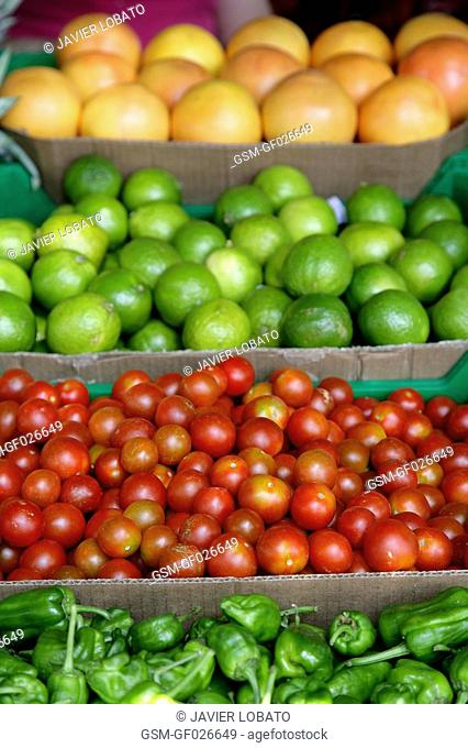 Cherry tomatoes, limes, Padron green hot peppers and grapefruits on sale at the market place