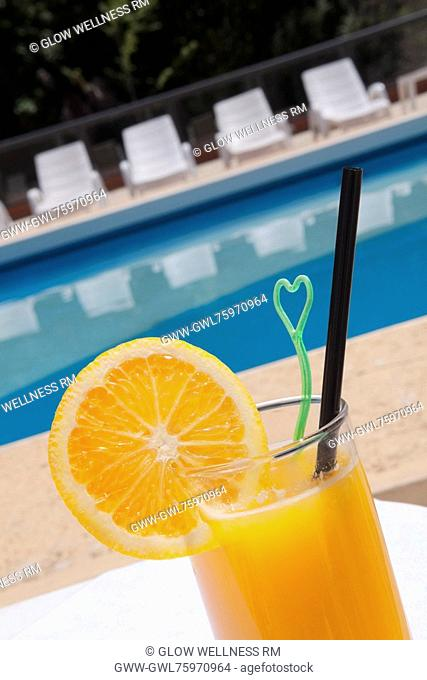 Glass of orange juice at the poolside