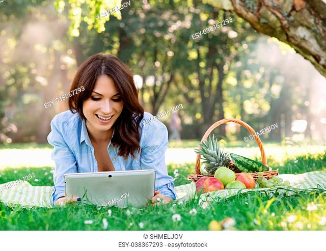Young attractive lady lying on a mat in the park browsing her tablet