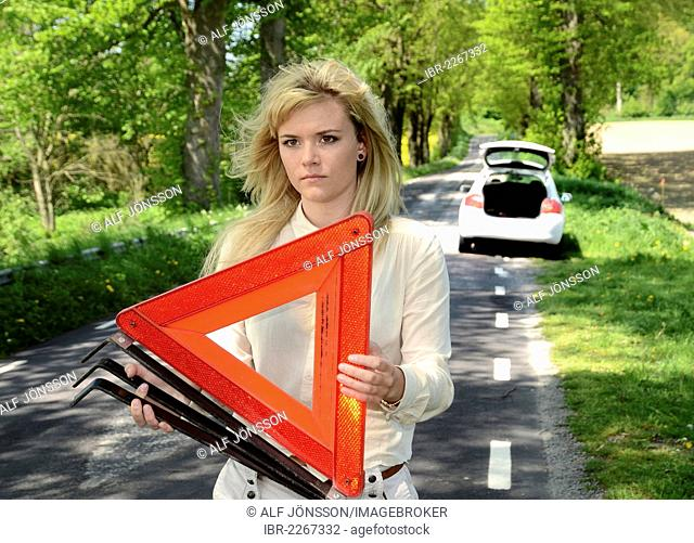 Woman with warning triangle at a road, Charlottenlund, Skåne, Sweden, Europe