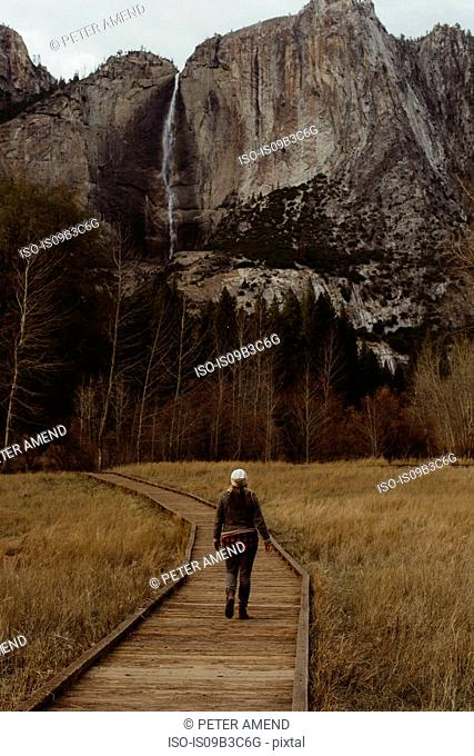 Rear view of female hiker hiking on boardwalk toward mountains, Yosemite National Park, California, USA
