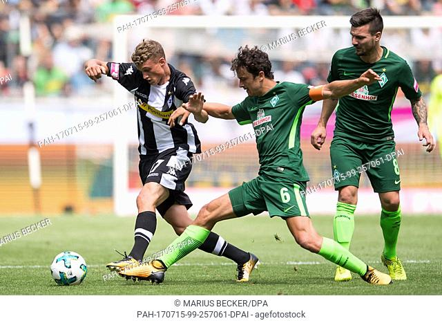 Gladbach's Mickael Cuisance (L) and Bremen's Thomnas Delaney (C) vie for the ball during the Telekom Cup's test match between Borussia Moenchengldbach and SV...