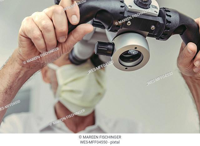 Dentist using microscope, portrait