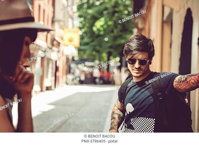 Portrait of a young man waiting on a street, urban environment